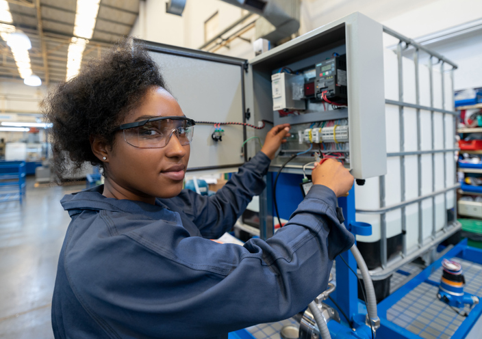 Black woman working at a manufacturing watre pump plant smiling at camera