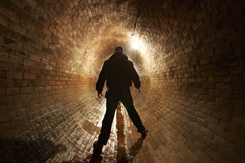 man in underground waste tunnel