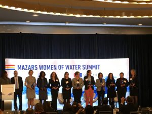 The recipients of the Top 10 Most Influential Women in Water awards stand with the masters of ceremonies at the Women of Water Summit. Pictured are (left to right): Tifphani White-King, Jon Freedman, Eleanor Allen, Nadine Leslie, Karen Sands, Christine Boyle, Karen Pallansch, Sarah Stevenson, Diane VanDe Hei, Adrienne Esposito, Bernadette Sohler, and Debra Coy. Mariah Walters Orose/WEF